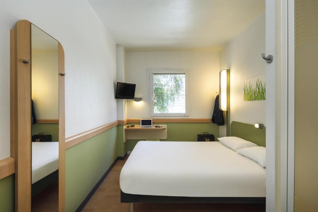 Een bed of bedden in een kamer bij Ibis Budget Málaga Centro