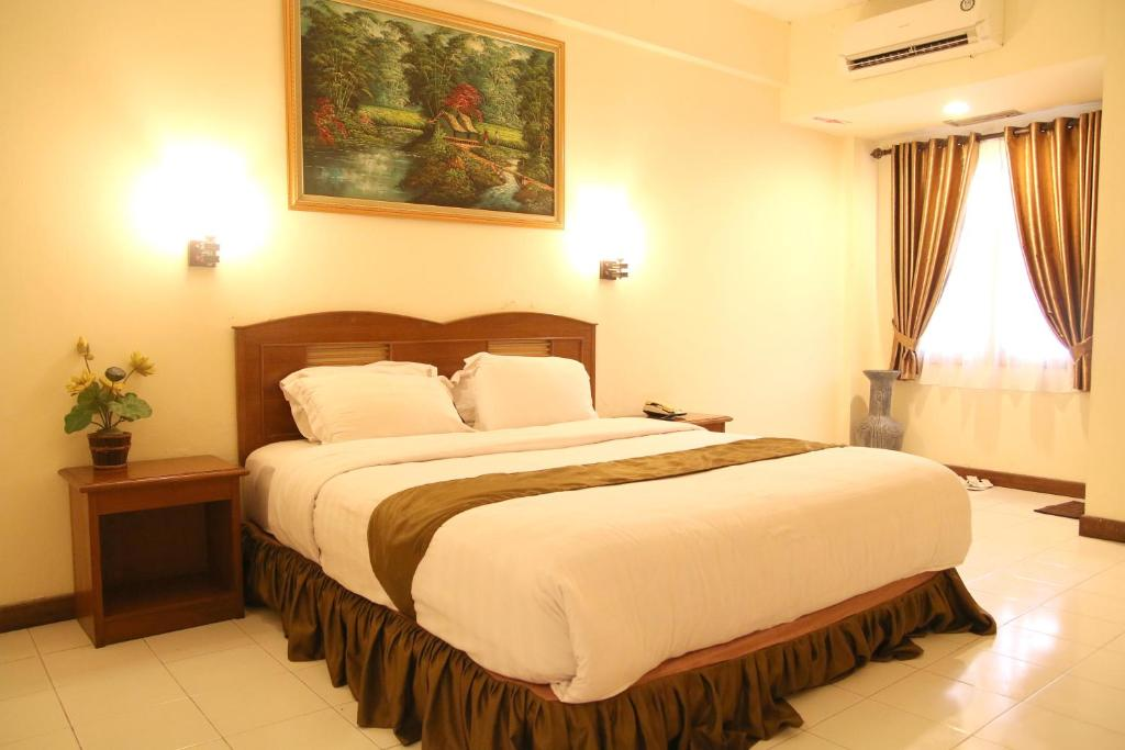A bed or beds in a room at Candisari Hotel