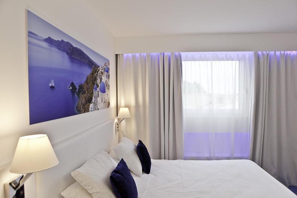 A bed or beds in a room at Privilège Hôtel & Apparts Eurociel Centre Comédie
