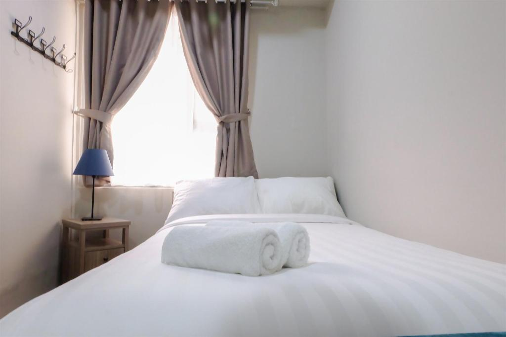 A bed or beds in a room at Spacious 1BR Pool View Menteng Square Apartment By Travelio