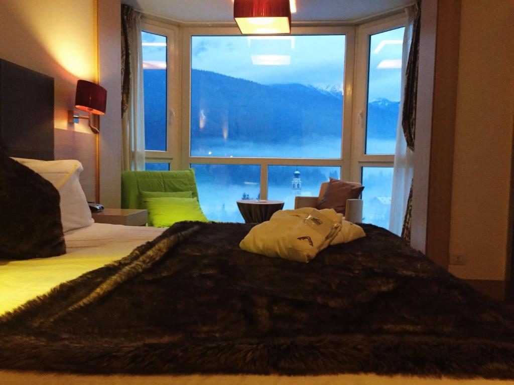 A bed or beds in a room at Antelao Dolomiti Mountain Resort