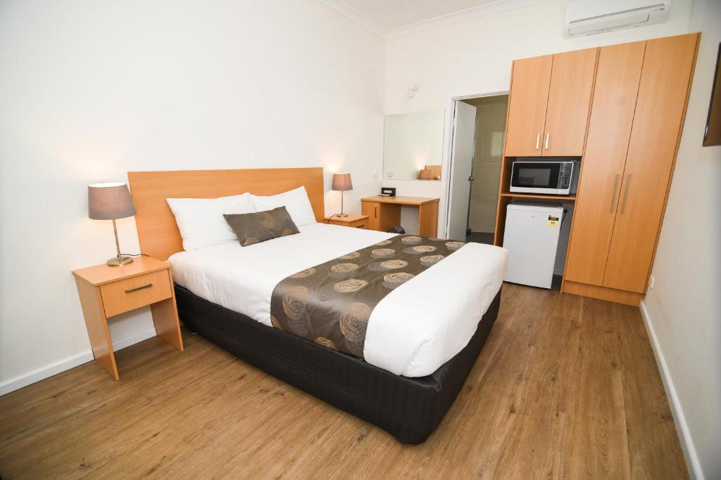 A bed or beds in a room at Dandenong Motel