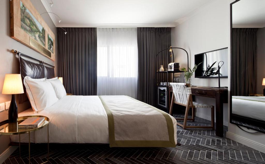 A bed or beds in a room at The Rothschild Hotel - Tel Aviv's Finest