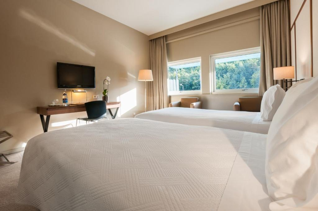 A bed or beds in a room at Hotel de Guimaraes