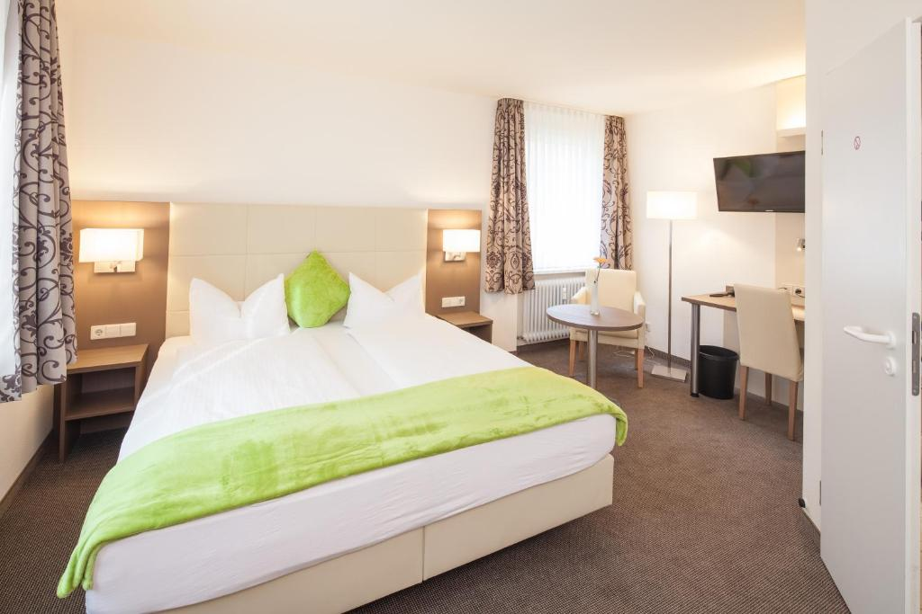 A bed or beds in a room at City Hotel Freiburg