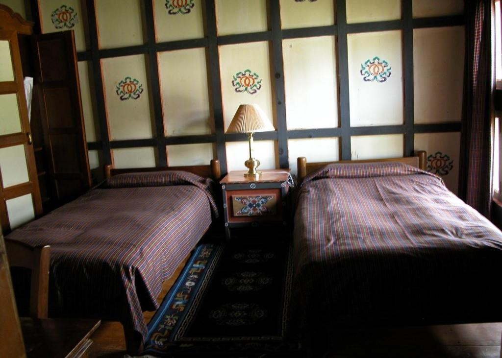 A bed or beds in a room at Gangtey Palace Hotel