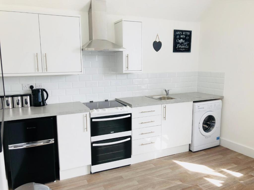 A kitchen or kitchenette at Modern Central Studio and One Bed Flats Close to the Beach