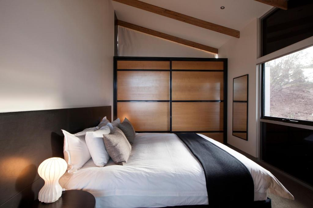 A bed or beds in a room at MONA Pavilions
