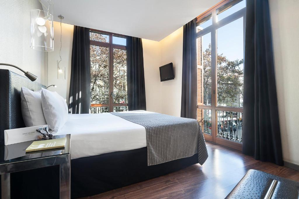 A bed or beds in a room at Exe Ramblas Boquería