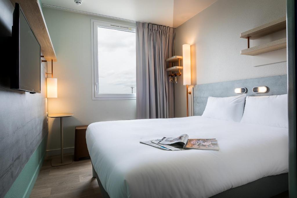 Un pat sau paturi într-o cameră la ibis budget Paris Gennevilliers