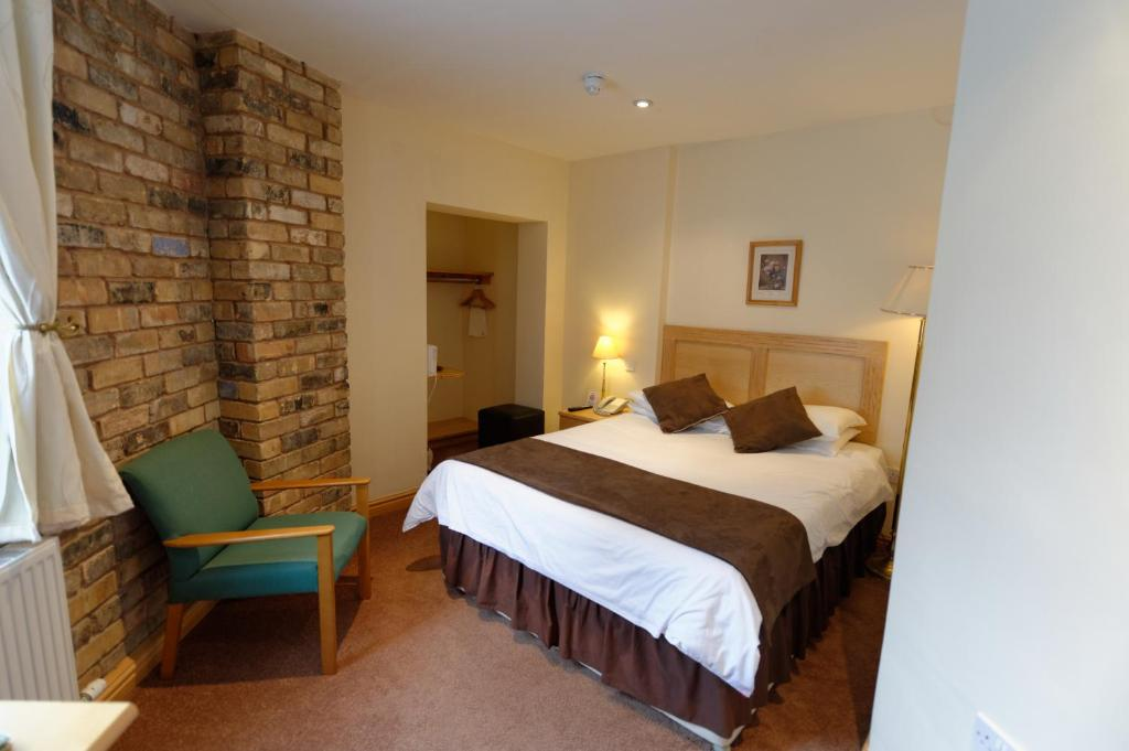 A bed or beds in a room at The Sleepwell Inn