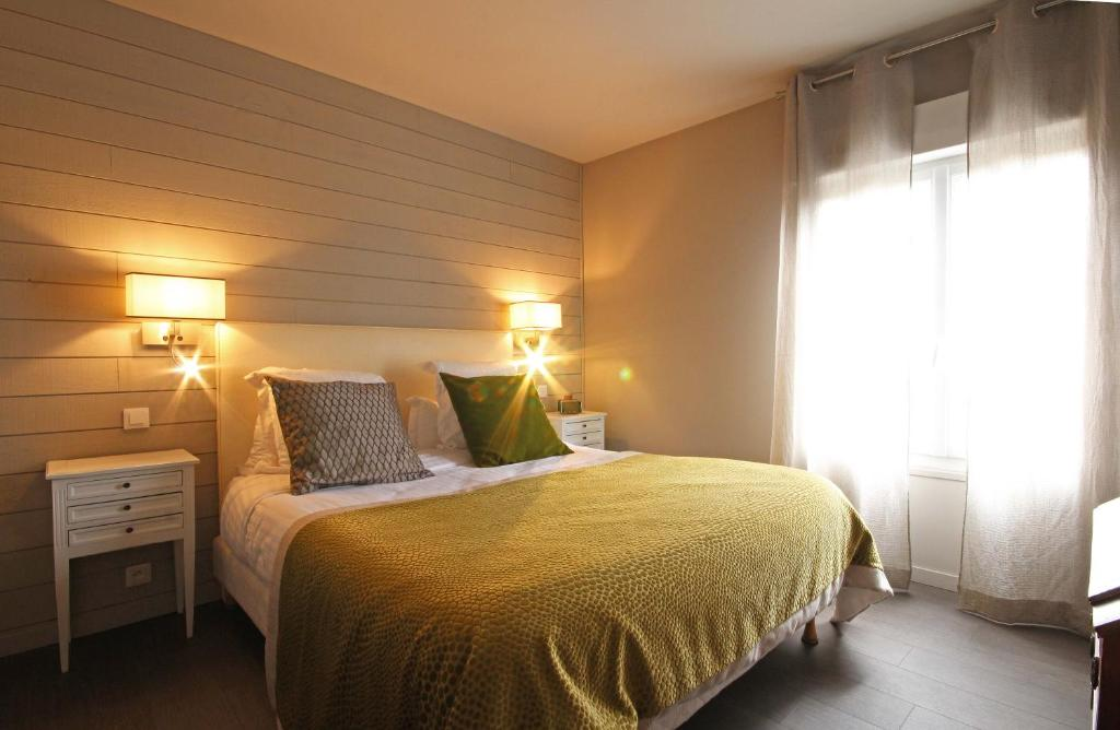 A bed or beds in a room at Le Faisan Dore