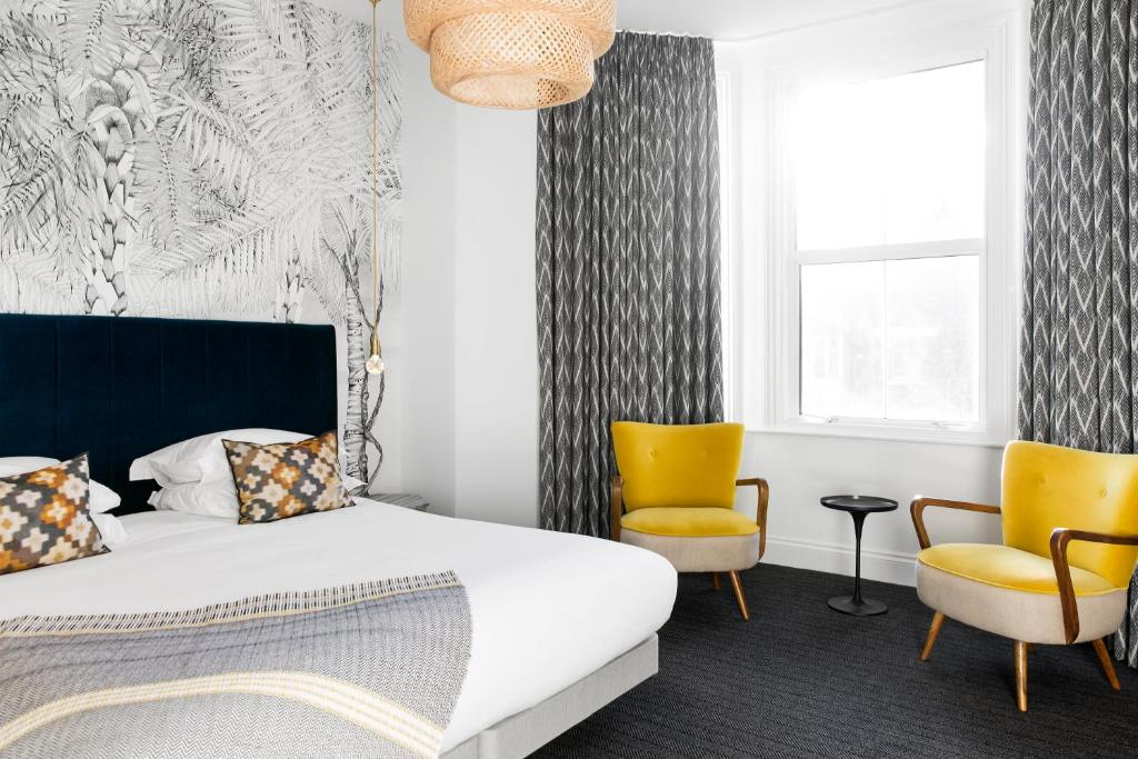 A bed or beds in a room at The Lodge Hotel - Putney