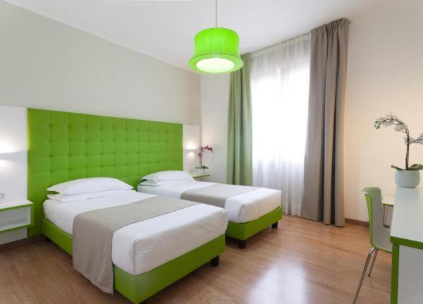 Un ou plusieurs lits dans un hébergement de l'établissement Hotel Milano Palmanova