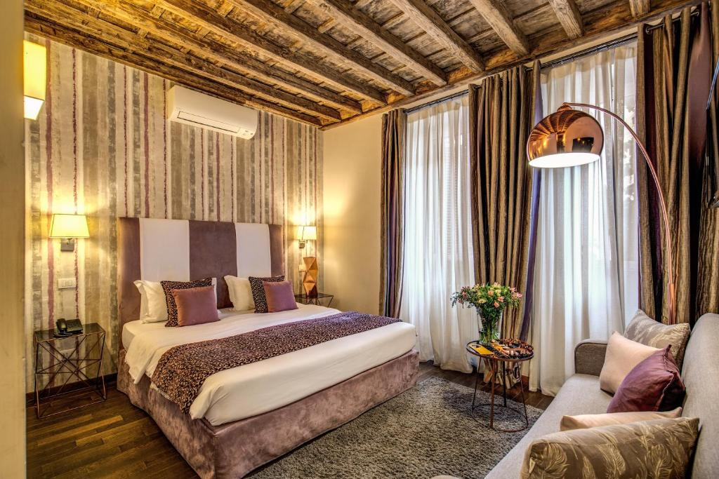 A bed or beds in a room at Trevi Beau Boutique Hotel