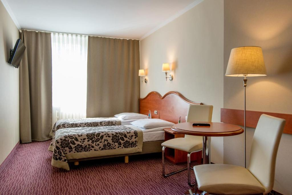 A bed or beds in a room at Hotel Krakus