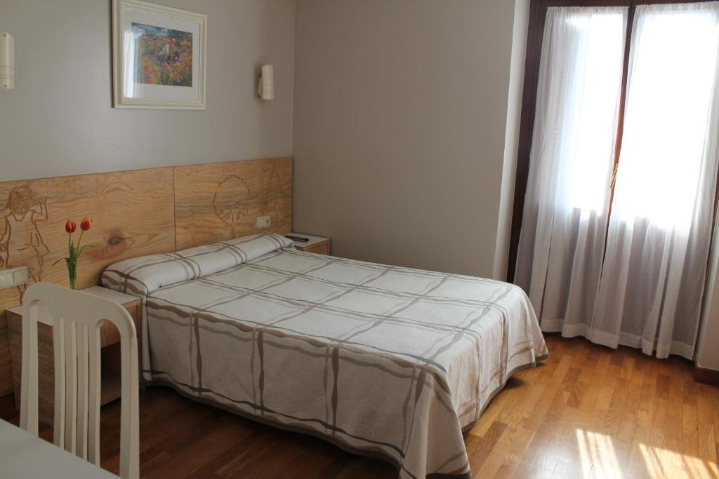 A bed or beds in a room at Pensión Lagunak