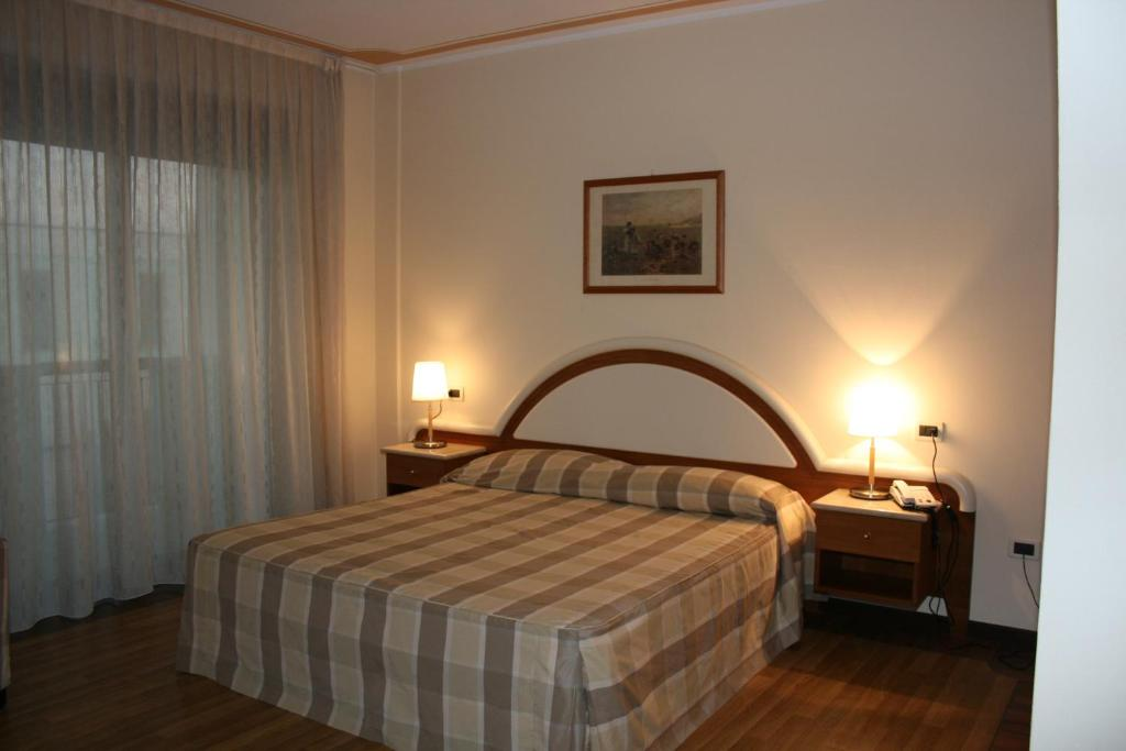 A bed or beds in a room at La Fonte Hotel