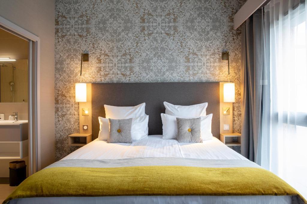 A bed or beds in a room at James Boutique Hôtel Colmar centre