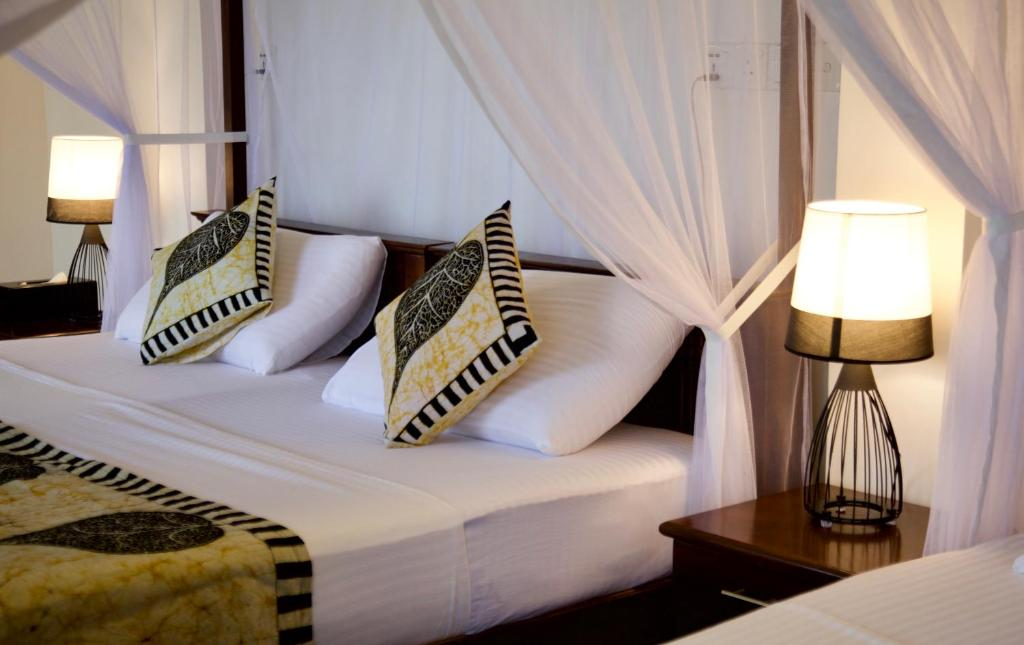 A bed or beds in a room at Glamour Mirissa