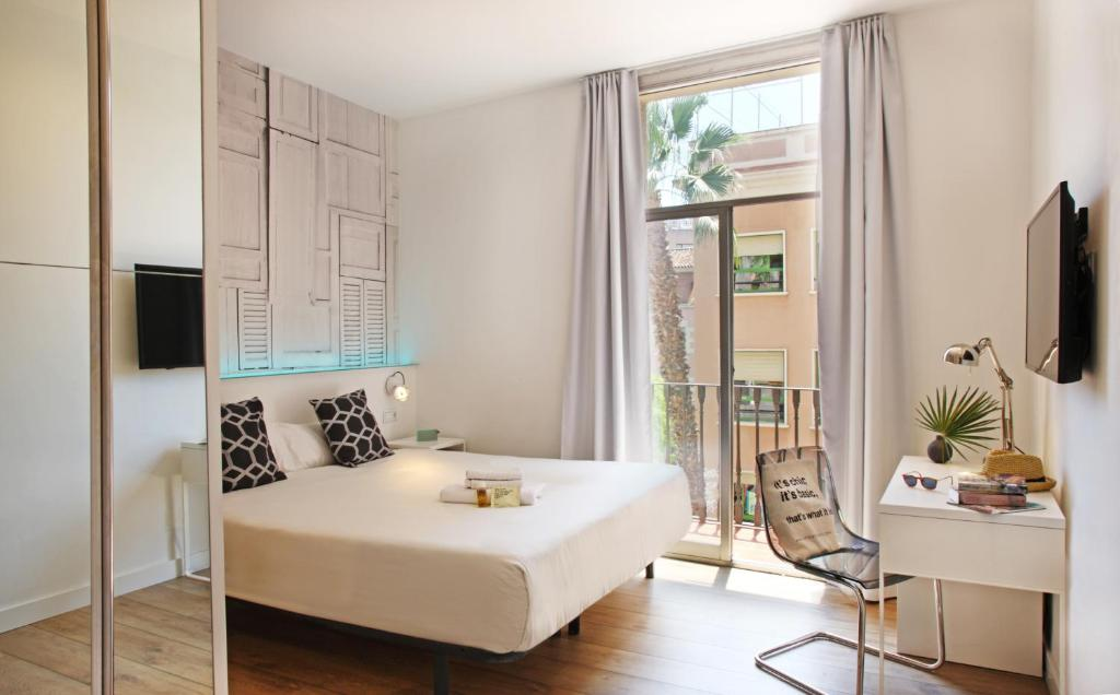 A bed or beds in a room at Chic & Basic Tallers Hostal