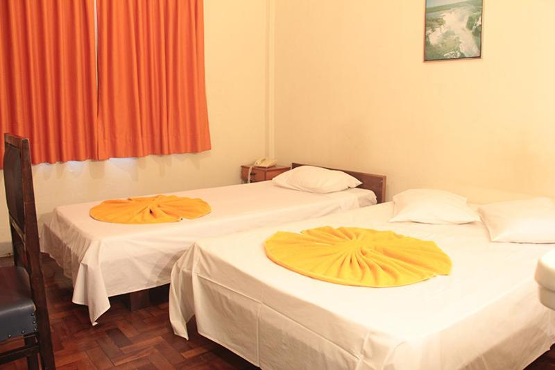 A bed or beds in a room at Hotel Indaiá