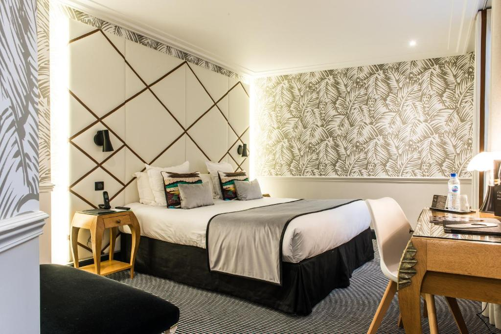 A bed or beds in a room at Hôtel Jardin Le Bréa