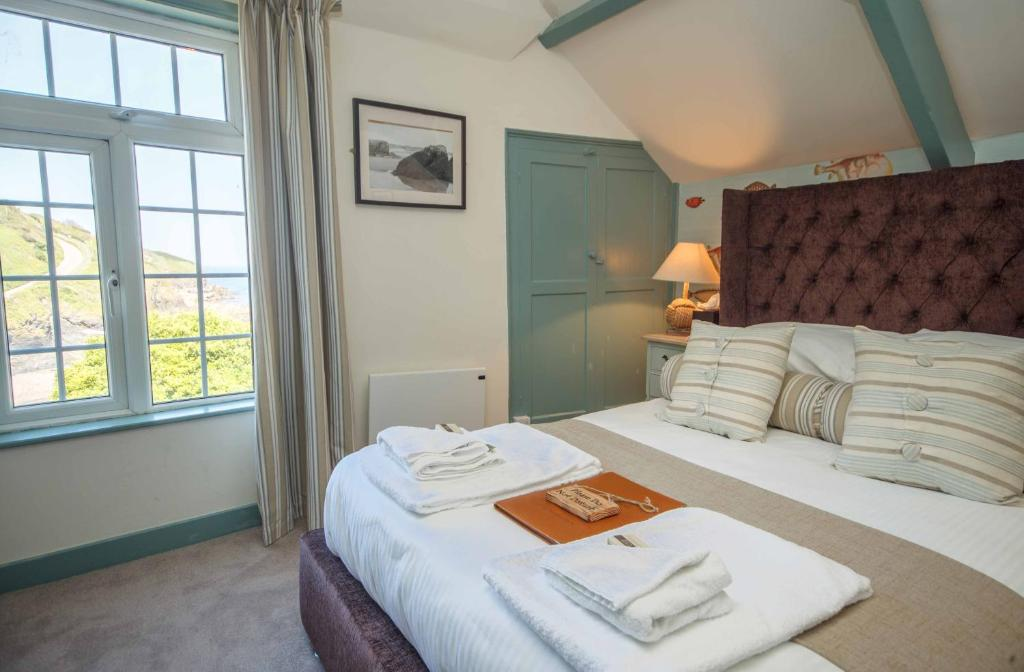 A bed or beds in a room at Port Gaverne Hotel