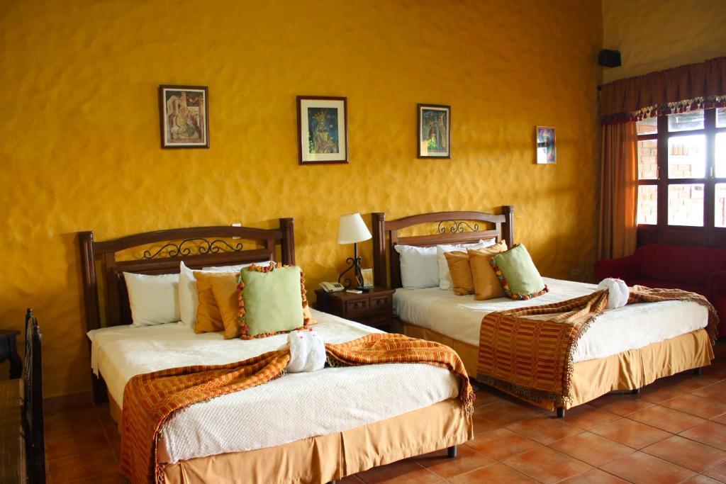A bed or beds in a room at La Posada de Suchitlan