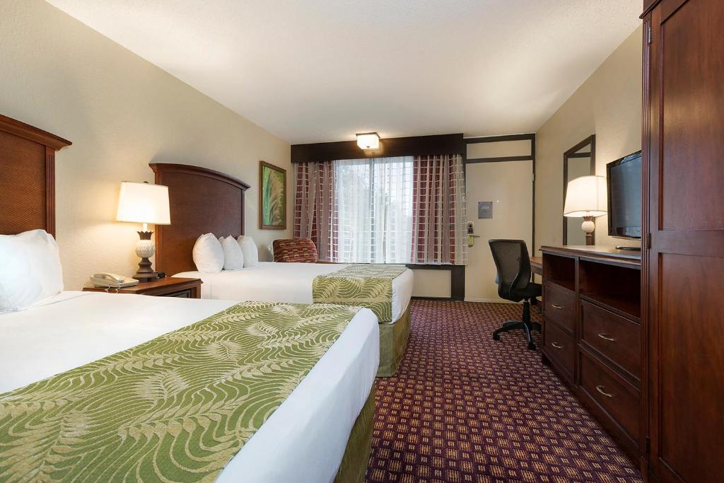 A bed or beds in a room at Rosen Inn at Pointe Orlando