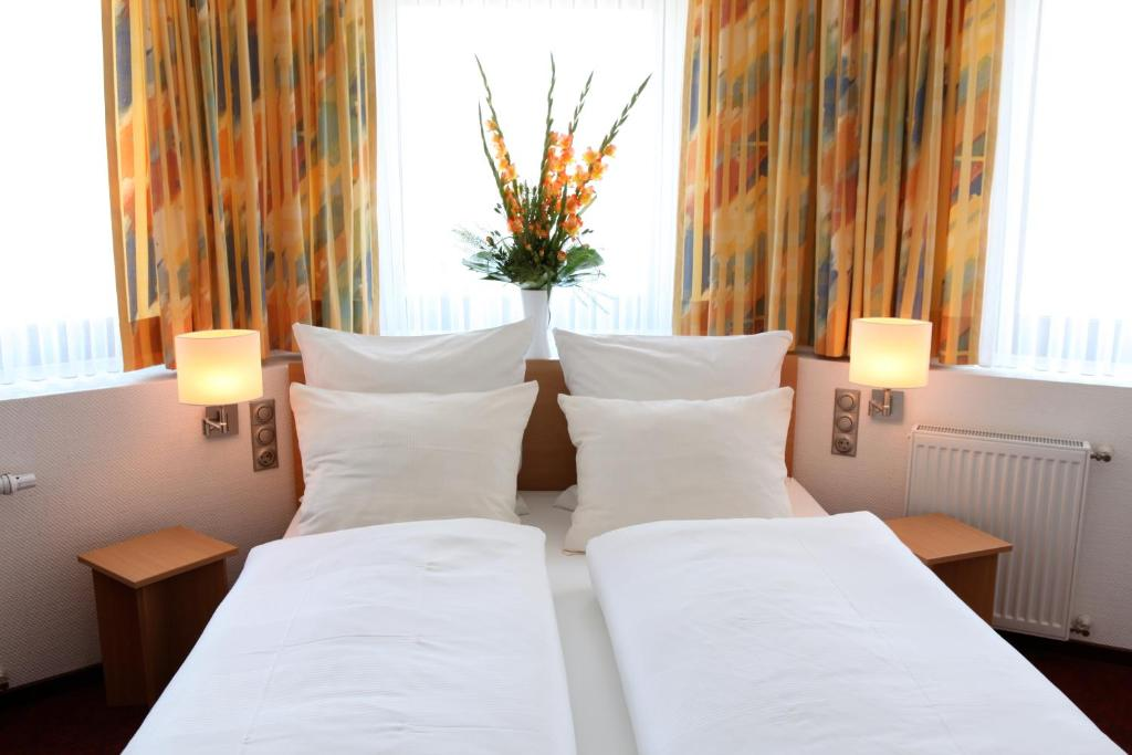 A bed or beds in a room at Akzent Hotel Oberhausen