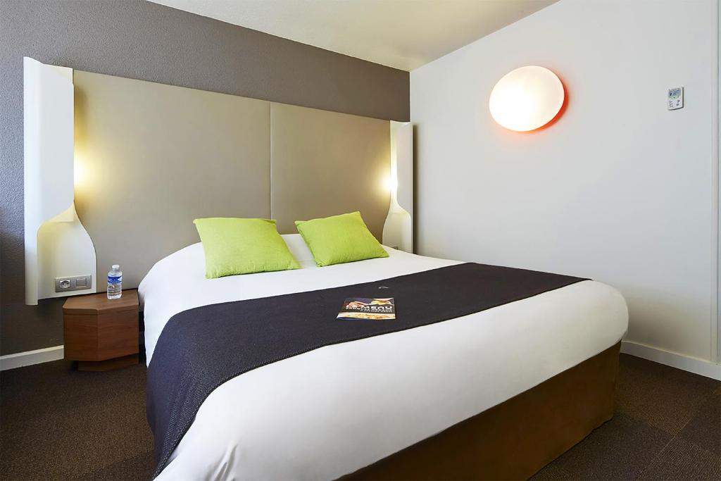 A bed or beds in a room at Campanile Roissy - Saint Witz