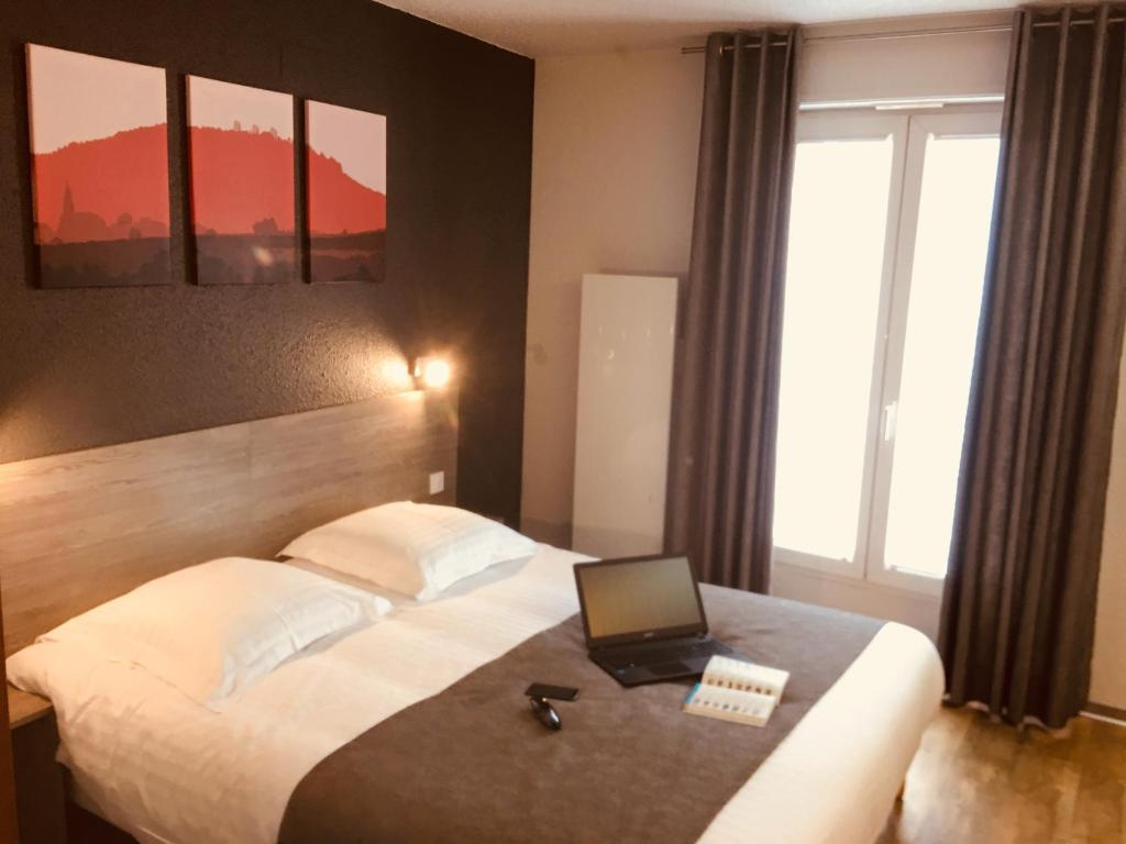 A bed or beds in a room at Hotel Colmar Vignes Eguisheim