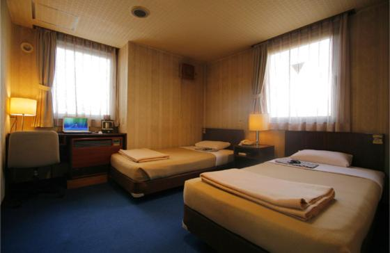 A bed or beds in a room at Hotel Kangetsuso