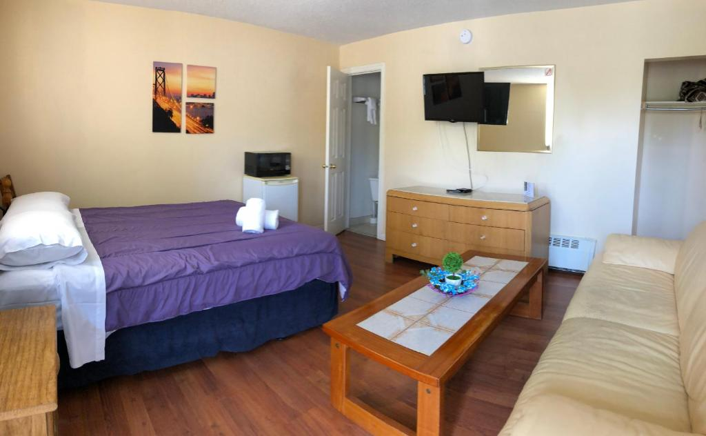 A bed or beds in a room at Wasaga Motel Inn