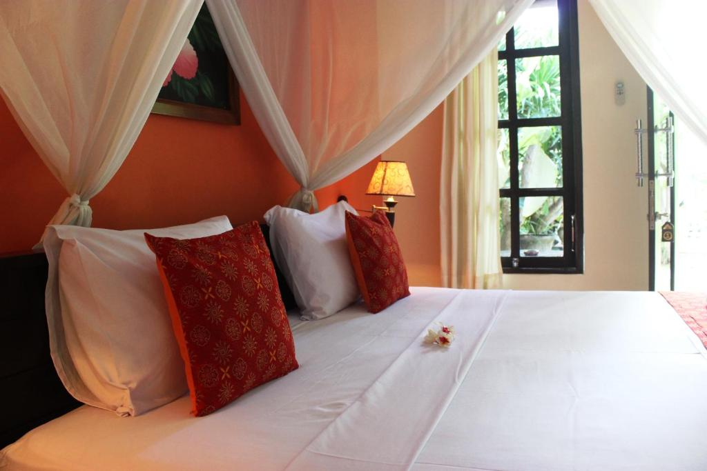 A bed or beds in a room at Giri Sari Guest House Pemuteran Bali