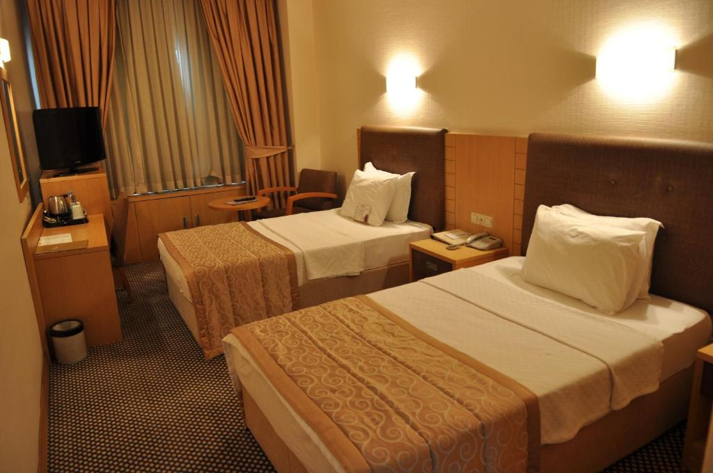 A bed or beds in a room at Surmeli Adana Hotel