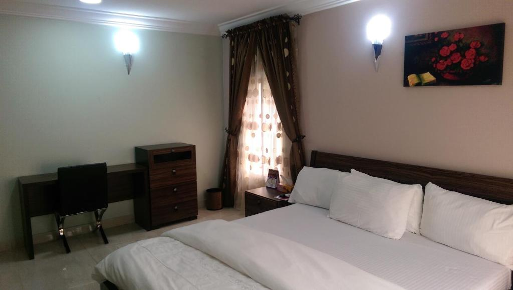 A bed or beds in a room at KH Lodge Abuja