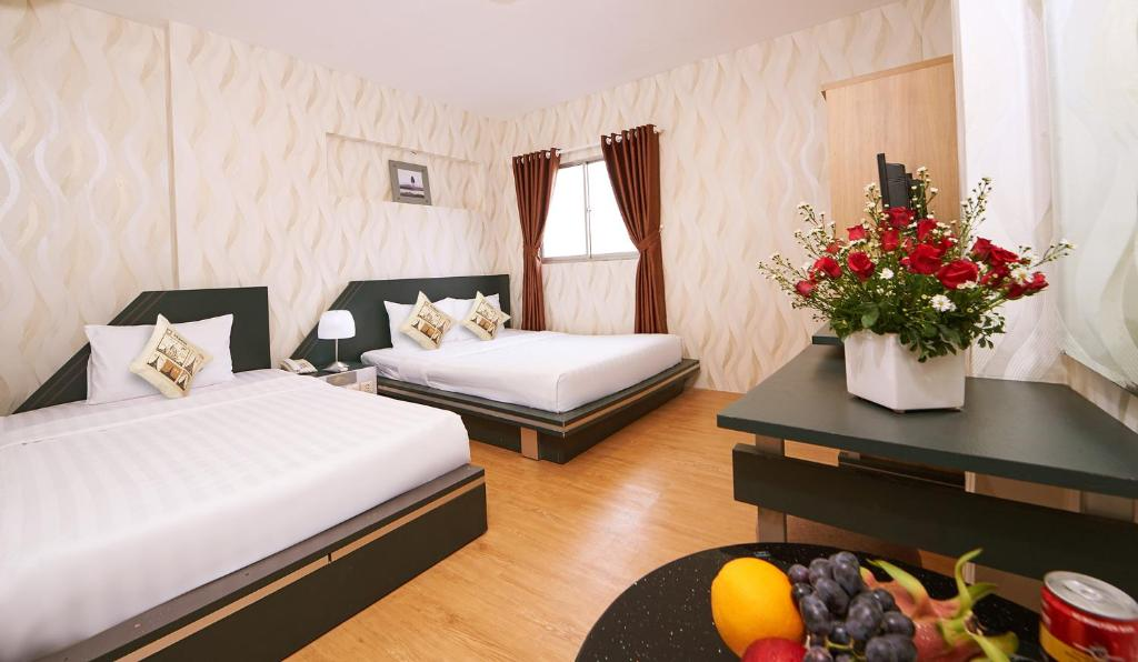 A bed or beds in a room at Saigon Charm Hotel