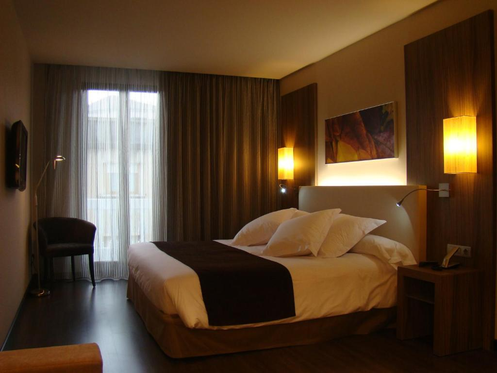 A bed or beds in a room at Hotel Aroi Ponferrada