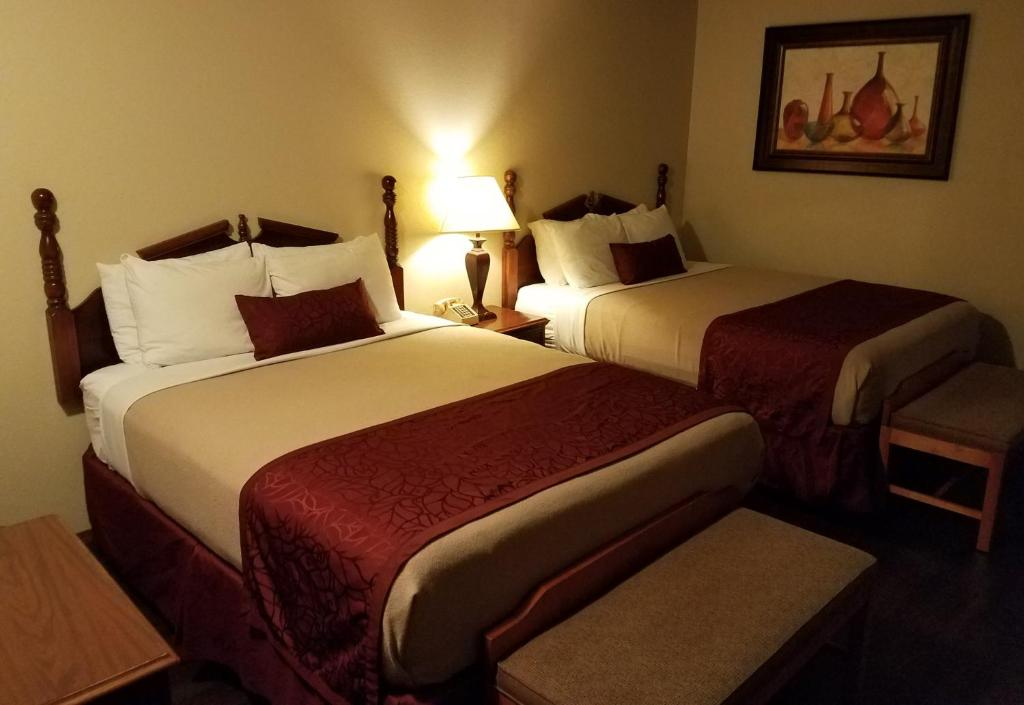 A bed or beds in a room at Homestead Motel