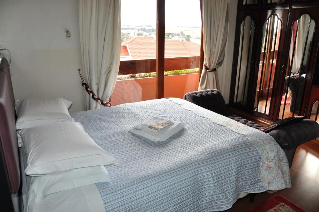 A bed or beds in a room at Pousada Monte Carlo