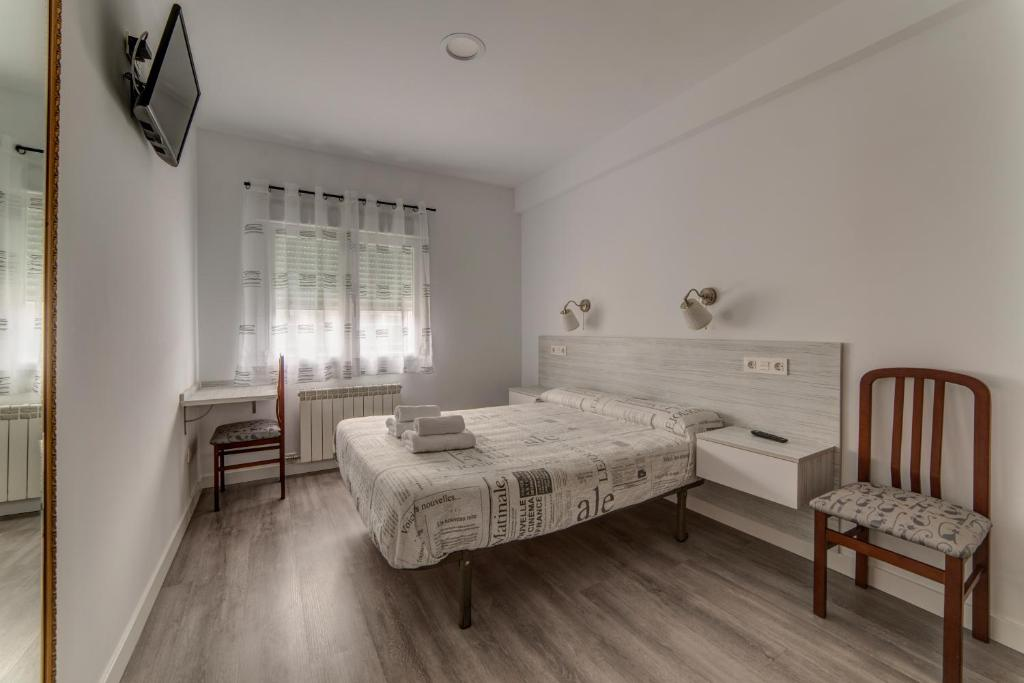 A bed or beds in a room at Hostal Lar