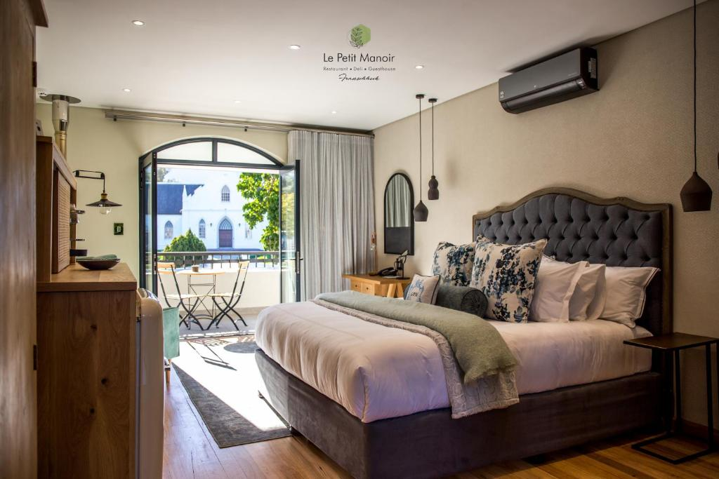A bed or beds in a room at Le Petit Manoir Franschhoek