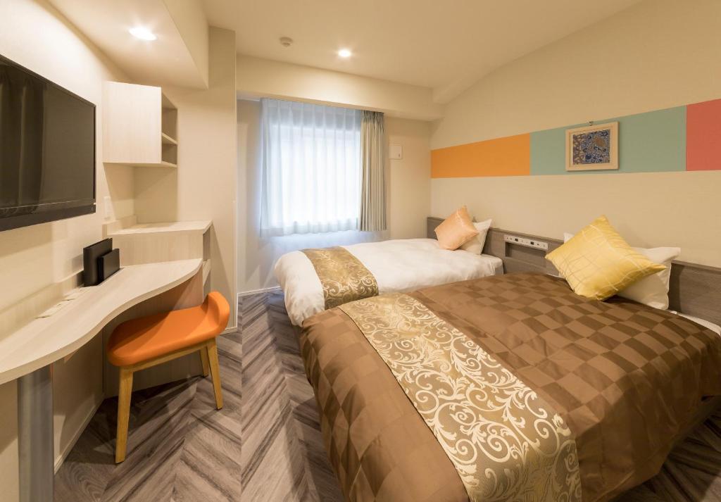 A bed or beds in a room at SARASA HOTEL Shin-Osaka