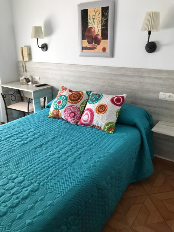A bed or beds in a room at Hostal Argentina