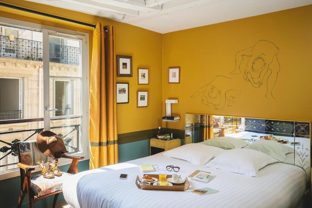 A bed or beds in a room at Hôtel Crayon by Elegancia