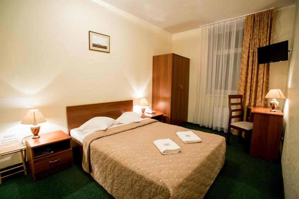 A bed or beds in a room at Dinaburg SPA Hotel