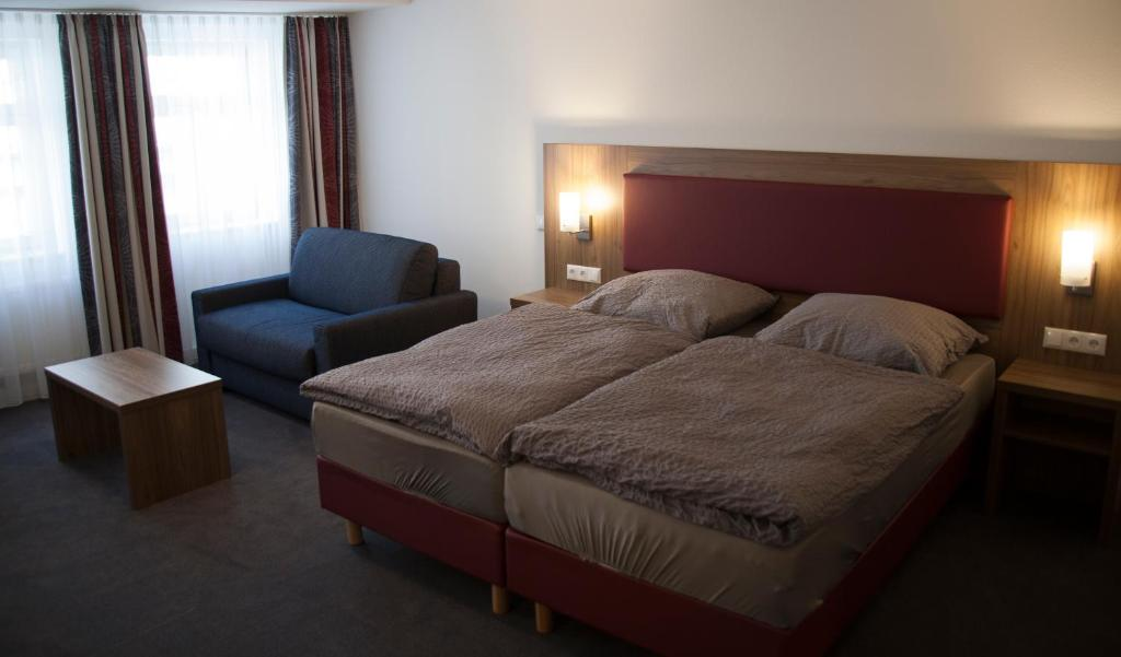 A bed or beds in a room at La Flamme Wertheim garni