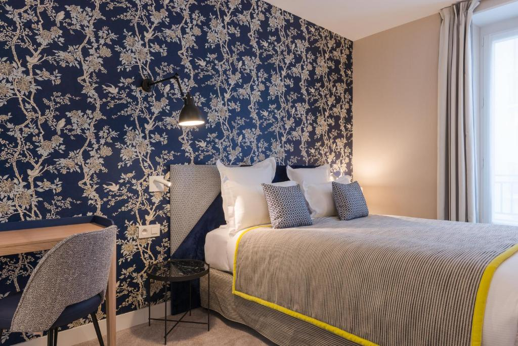 A bed or beds in a room at Hotel Le Mareuil